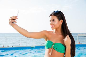 Woman in bikini making selfie photo outdoors