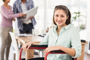 Smiling casual businesswoman in wheelchair