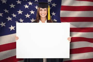 Woman in her graduation gown holds a blank sign