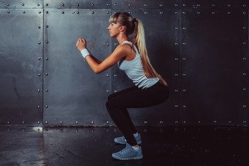 Athletic young woman fitness model warming up doing squats