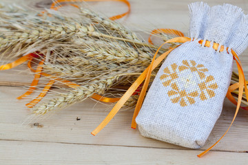 Sachet with ukrainian embroidery, wheat and oat on wooden background