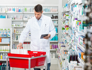 Pharmacist Counting Stock While Holding Digital Tablet In Drugst