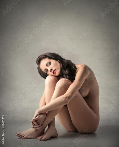 naked woman sitting on cake