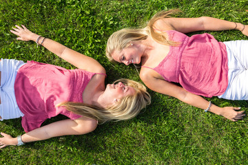 two women lying on the grass head to head looking at each other