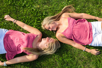 two young women lying on the grass head to head looking at each