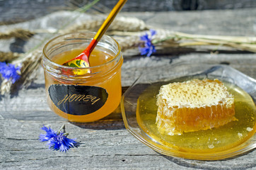 Honey in honeycomb on the glass plate and little jar with russian spoon  with ears and cornflowers on the wood background, selective focus