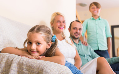 parents with two children posing in home interior