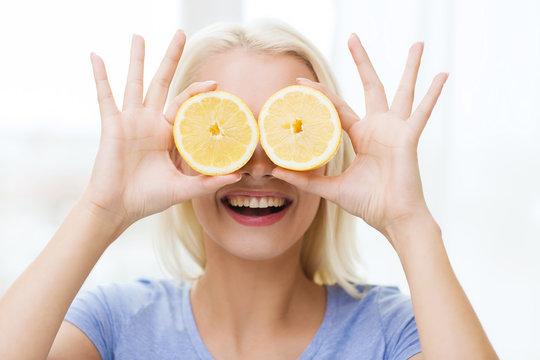 happy woman having fun covering eyes with lemon