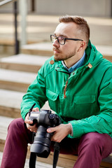 young hipster man with digital camera in city