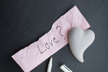 Hand-written text Love? on a piece of wrinkled paper, one heart of stone and a pencil