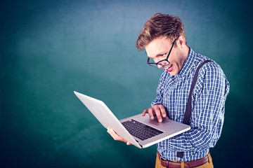 Composite image of geeky businessman using his laptop