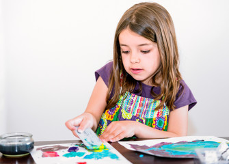 Expressive portrait of a pretty young girl doing paint