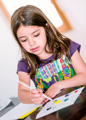 Portrait of cute girl concentrated while painting