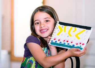 Portrait of a beautiful girl showing her drawing