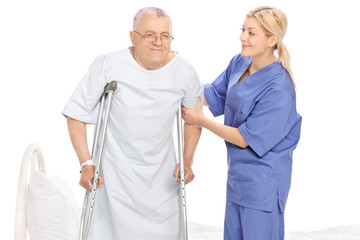 Young female nurse helping a senior patient with crutches