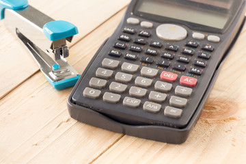 Calculator and Stapler on Wooden board