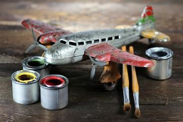 altes Blechflugzeug mit Farbtöpfen und Pinseln zur Restauration