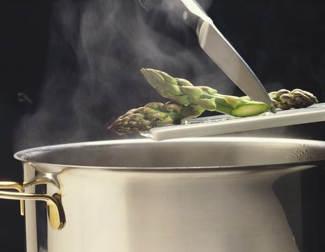 Green asparagus tips going into a steaming pan