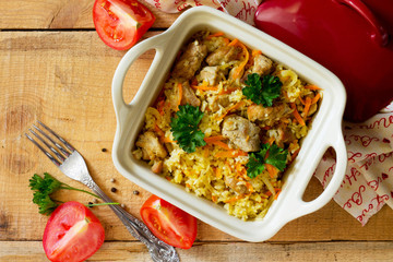 Pilaf with meat in a pot on a wooden table, top view