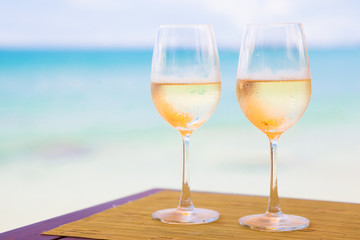 two glasses of chilled white wine on table near the beach