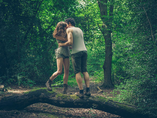 Young couple standing on log kissing
