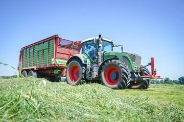 Fototapete - Traktor mit Ladewagen bei der Ernte von Gras für Silage