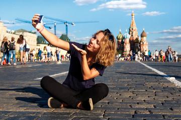 Красивая, молодая девушка фотографируется, сидя на Красной Площади, и посылает воздушный поцелуй