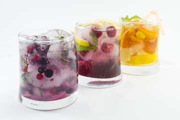Three non alcoholic fruit cocktails with iced and sliced fruit o