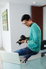 Asian Man Tethering DSLR To Laptop PC Downloading Photo