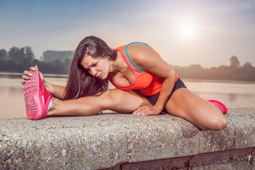 Fit girl stretching before running.
