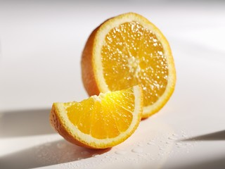 Orange wedge in front of half an orange