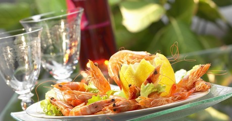 Prawns with lemons in a bowl and a glass of wine