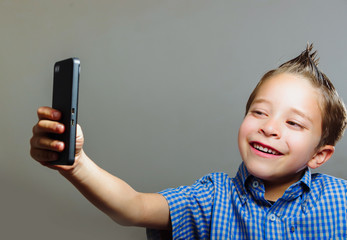 Cute boy taking a selfie with cell phone