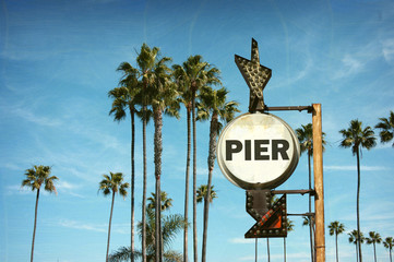 aged and worn vintage photo of pier sign on beach with palm trees