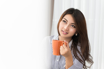 Beautiful asian woman drinking coffee at home