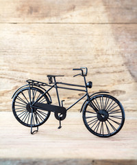 Vintage model black bicycle on old wooden table.