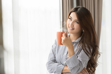 Asian Woman drinking coffee at home