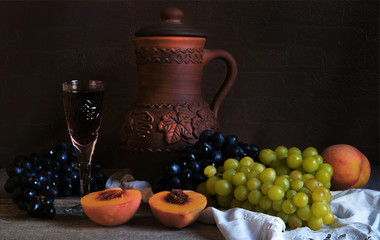 A pitcher, a glass of wine, fruits.