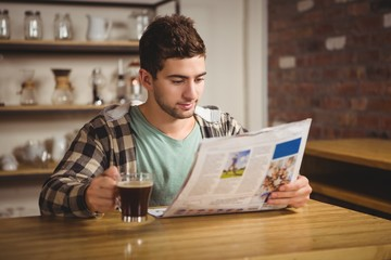 Hipster drinking coffee and reading newspaper