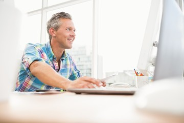 Smiling casual designer working with computer