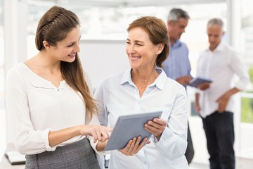 Smiling businesswomen using tablet in a meeting