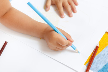 Adorable little girl drawing with pencils