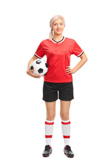 Young female football player holding a ball