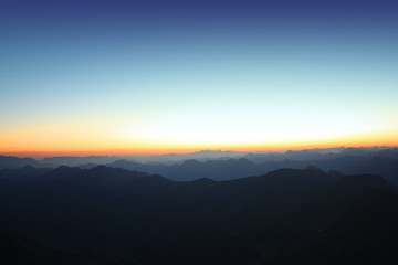 sunrise in the mountains, over the summits