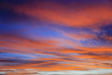 Fiery September evening skyscape with clouds lit by red sunset against a dark blue sky. UK Britain