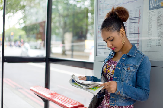 young woman reading a paper at the bus stop