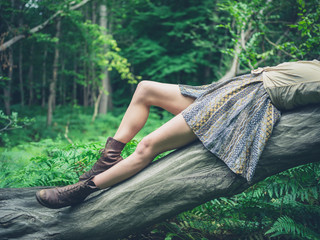 Young woman lying on fallen tree in forest