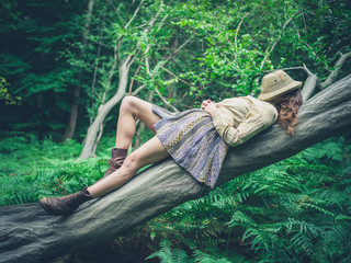 Young woman lying on tree in forest