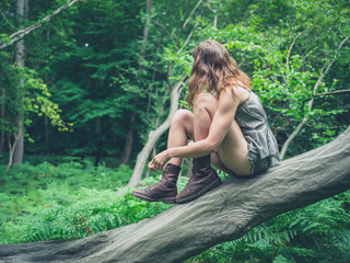 Young woman sitting on fallen tree in forest