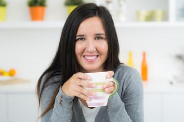 lächelnde junge frau trinkt tee